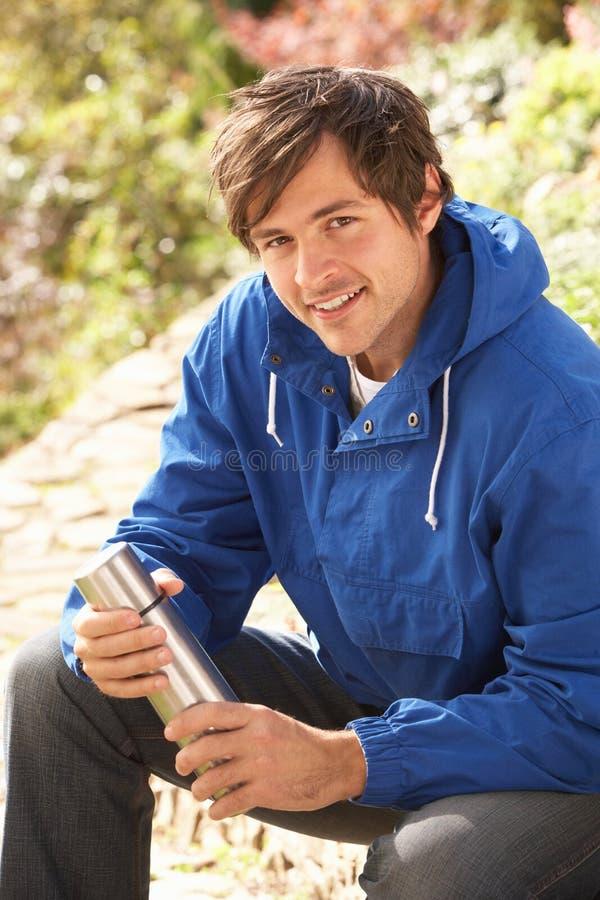 Junger Mann, der mit Thermos-Flasche im Herbst-La sich entspannt stockbild