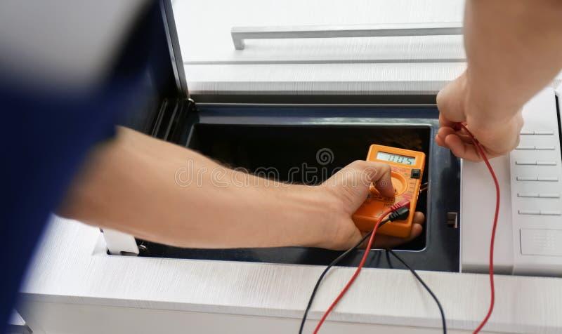 Junger Mann, der mit Vielfachmessgerätmikrowellenherd repariert stockfotografie