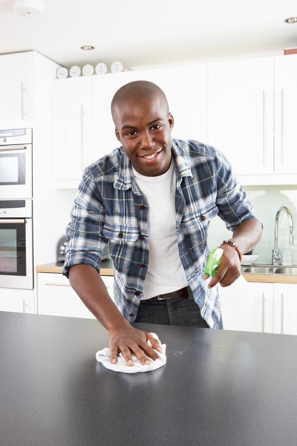 Junger Mann, der moderne Küche säubert stockbild