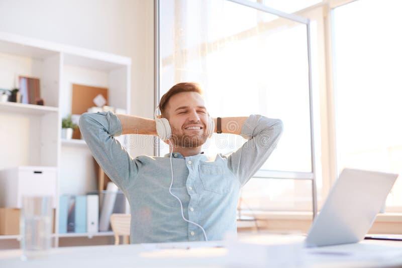 Junger Mann, der Musik am Arbeitsplatz hört lizenzfreie stockbilder