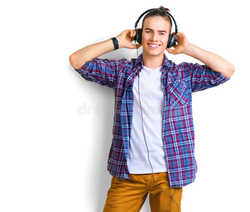 Junger Mann, der Musik in den Kopfhörern über Weiß genießt stockfotografie