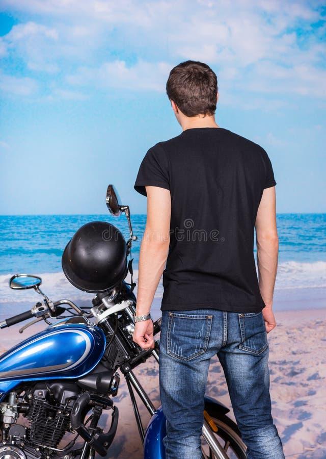 Junger Mann, der nahe bei Motorrad auf Strand steht stockfoto