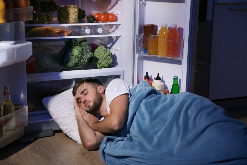 Junger Mann, der nahe Kühlschrank schläft stockbild
