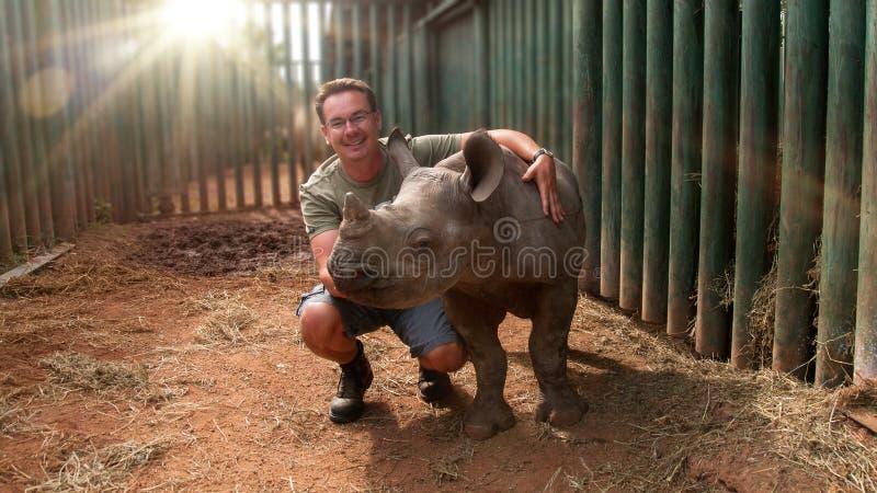 Junger Mann, der Nashornbaby berührt lizenzfreie stockfotos