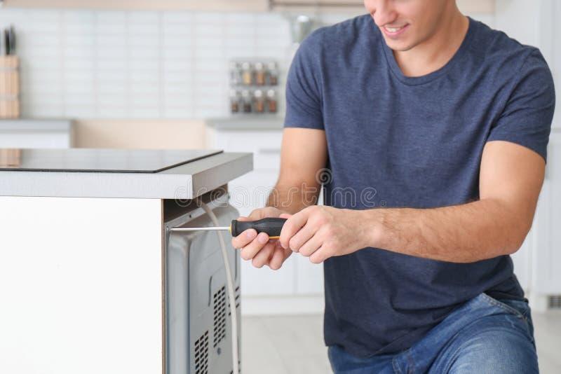 Junger Mann, der Ofen repariert, stockbild