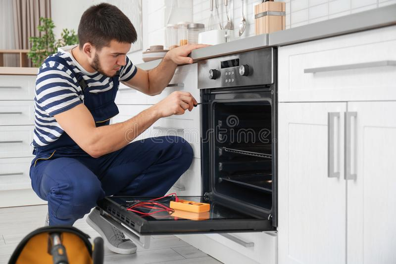 Junger Mann, der Ofen repariert stockfotos