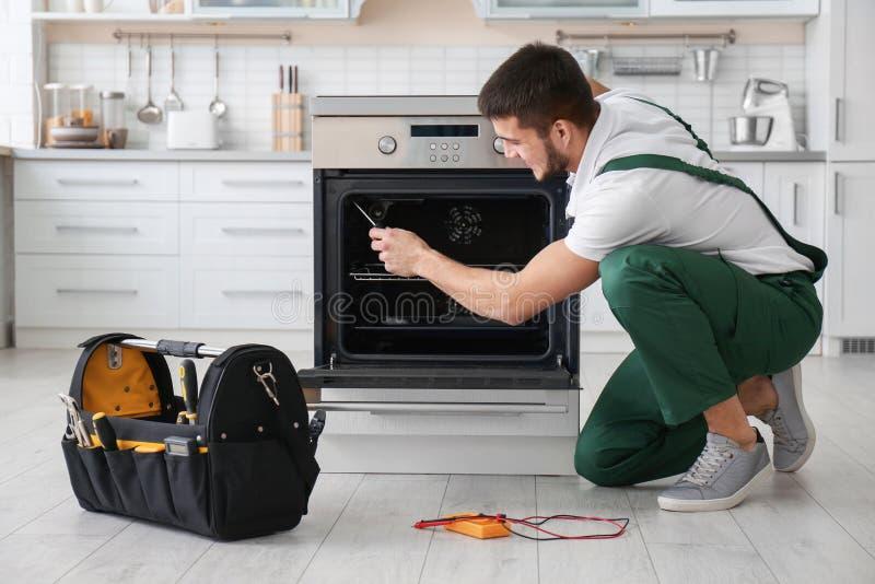 Junger Mann, der Ofen repariert stockbilder