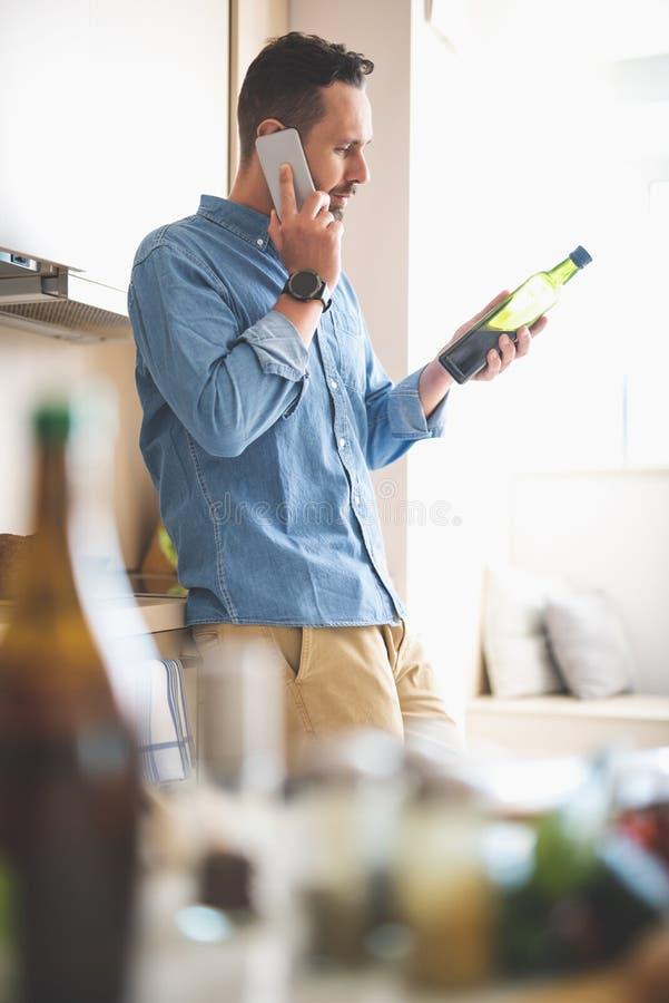 Junger Mann, der Olivenöl bei der Unterhaltung auf Mobiltelefon betrachtet stockbild