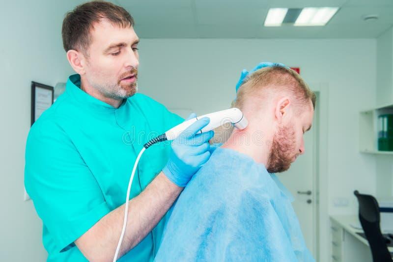 Junger Mann an der Physiotherapie, die Laser-Therapiemassage empfängt Ein Chiropraktor behandelt den zervikalen Dorn des Patiente lizenzfreie stockfotos