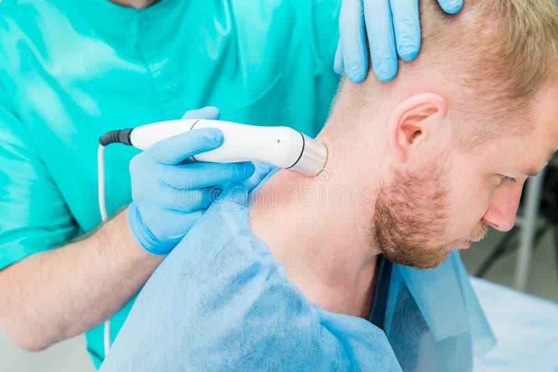 Junger Mann an der Physiotherapie, die Laser-Therapiemassage empf?ngt Ein Chiropraktor behandelt den zervikalen Dorn des Patiente lizenzfreies stockbild