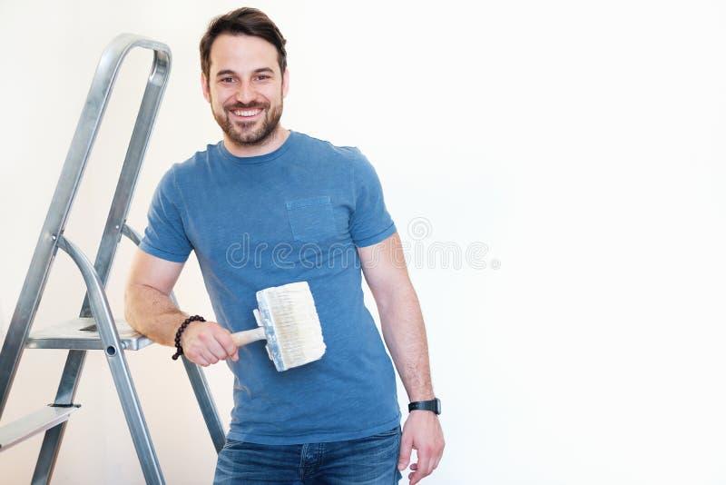 Junger Mann, der Pinsel auf weißem Hintergrund hält lizenzfreie stockbilder