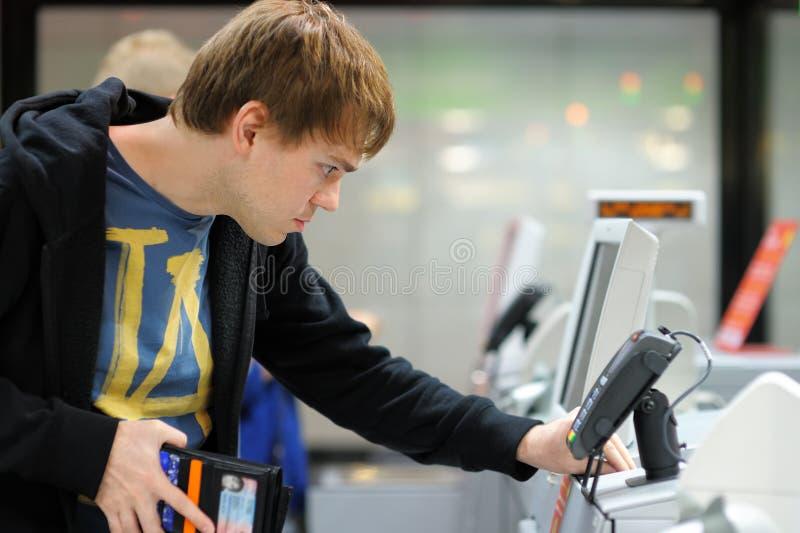Junger Mann, der Positions-Anschluss am Shop verwendet lizenzfreie stockfotografie