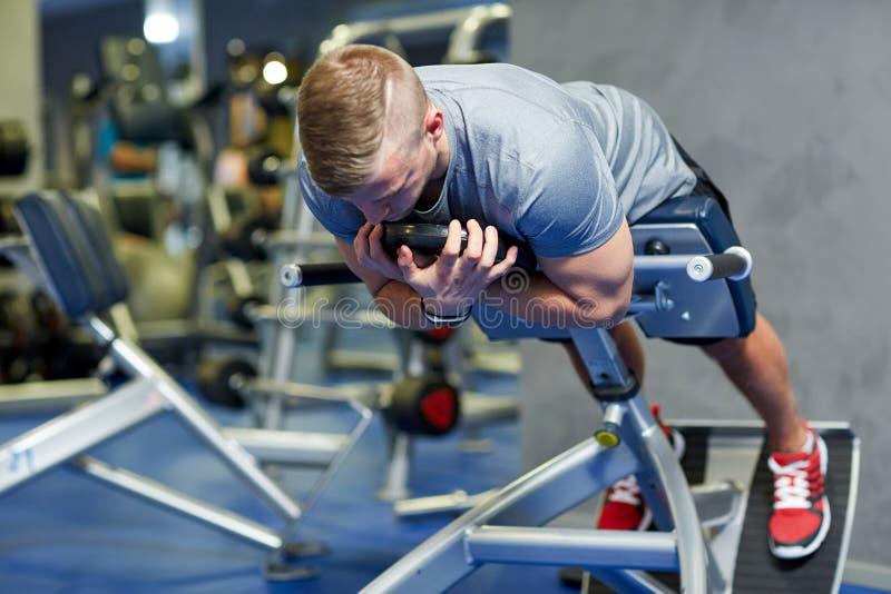 Junger Mann, der Rückenmuskulatur auf Bank in der Turnhalle biegt lizenzfreies stockbild