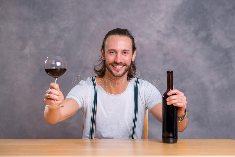 Junger Mann, der Rotwein trinkt stockbild