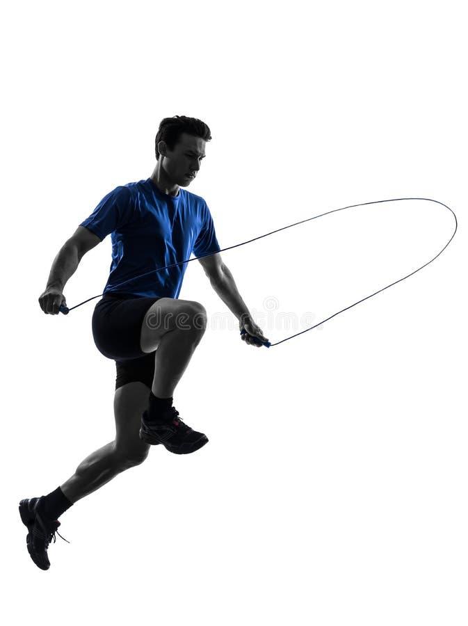 Junger Mann, der Schattenbild des springenden Seils ausübt stockfotografie
