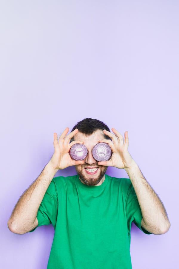 Junger Mann, der Scheiben der roten Zwiebel vor seinen Augen hält lizenzfreies stockfoto