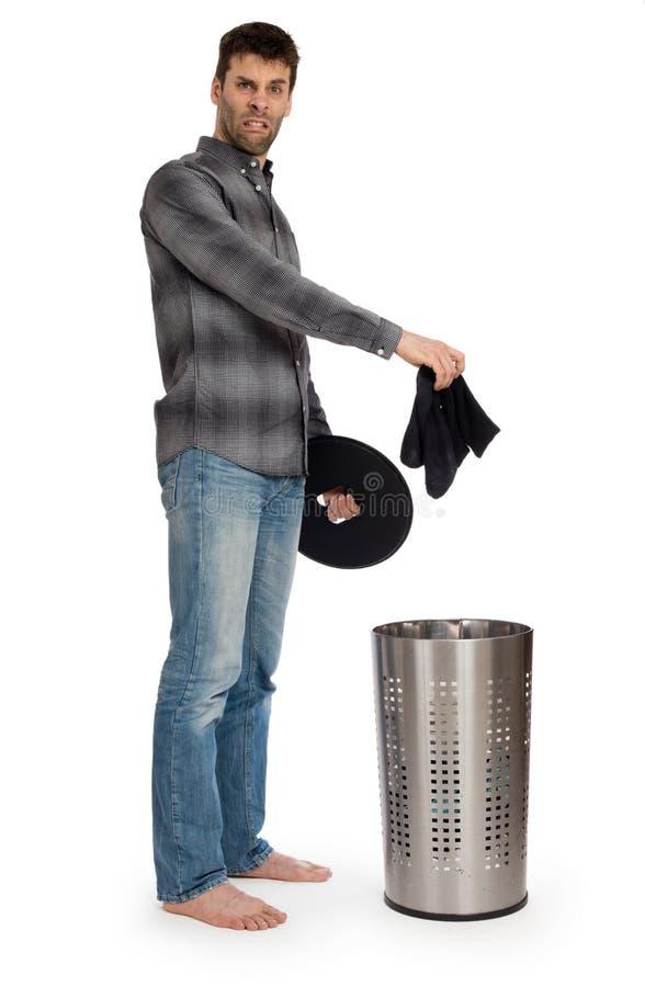 Junger Mann, der schmutzige Socken in einen Wäschekorb einsetzt stockfotografie