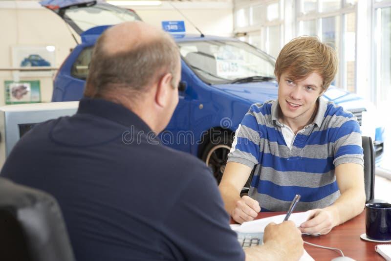 Junger Mann, der Schreibarbeit im Autoausstellungsraum ausfüllt lizenzfreie stockfotos