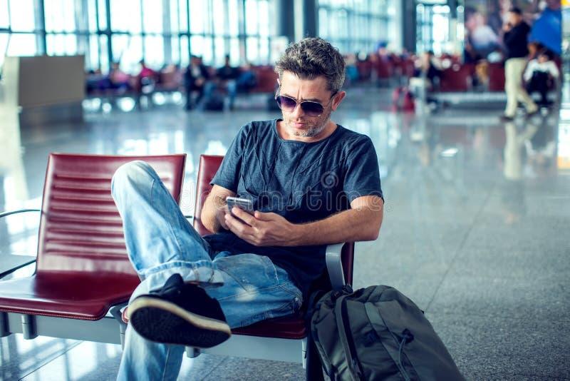 Junger Mann, der sein Telefon bei der Aufwartung seines Fluges in der Luft überprüft stockbilder