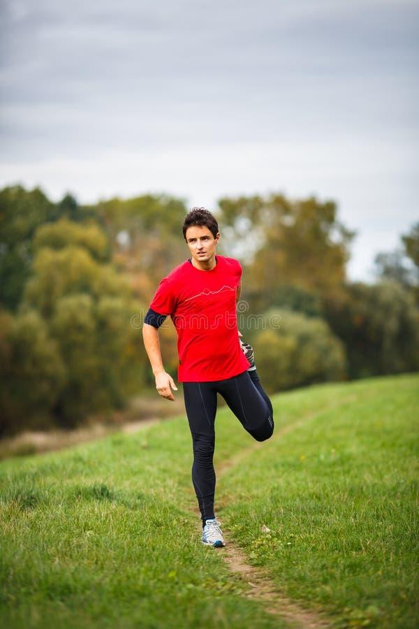 Junger Mann, der seine Beine ausdehnt stockfotografie