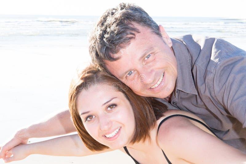 junger Mann, der seine Freundin auf seinem am Strand zurückbringt stockfotografie