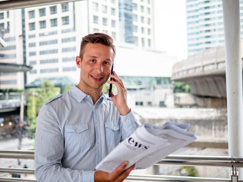 Junger Mann, der an seinem Telefon beim Ablesen der Zeitungen an einem Morgen gegen den Hintergrund einer modernen Stadt spricht lizenzfreies stockbild