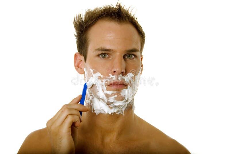Junger Mann, der seinen Bart rasiert lizenzfreies stockfoto