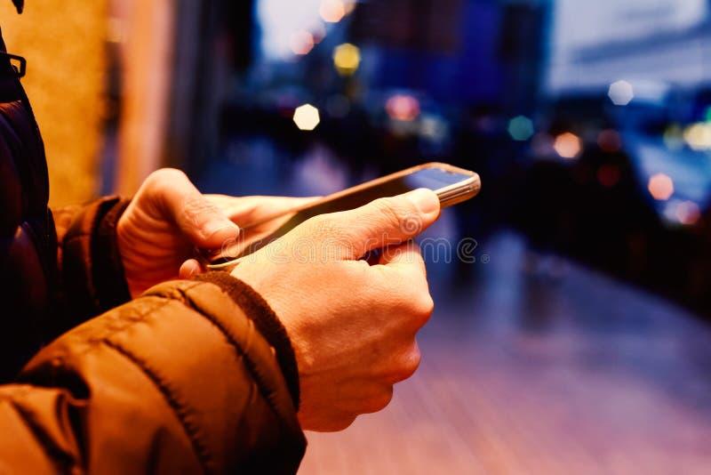 Junger Mann, der seinen Smartphone in der Straße nachts verwendet lizenzfreies stockbild