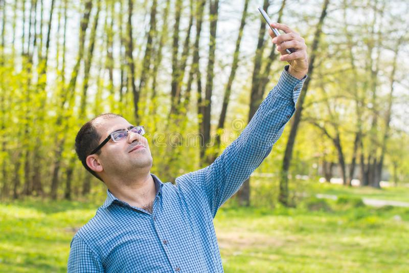 Junger Mann, der selfie im Wald nimmt stockbilder