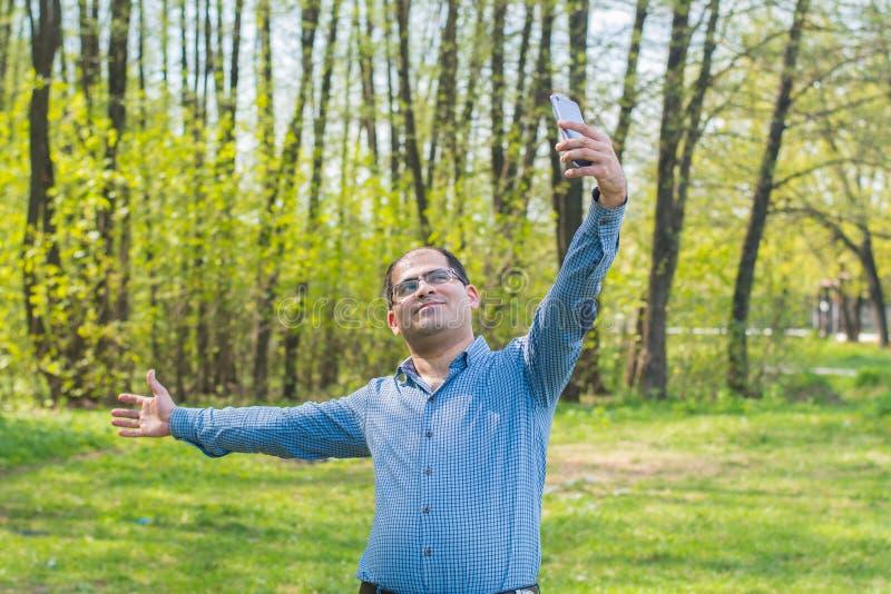 Junger Mann, der selfie im Wald nimmt lizenzfreie stockfotografie