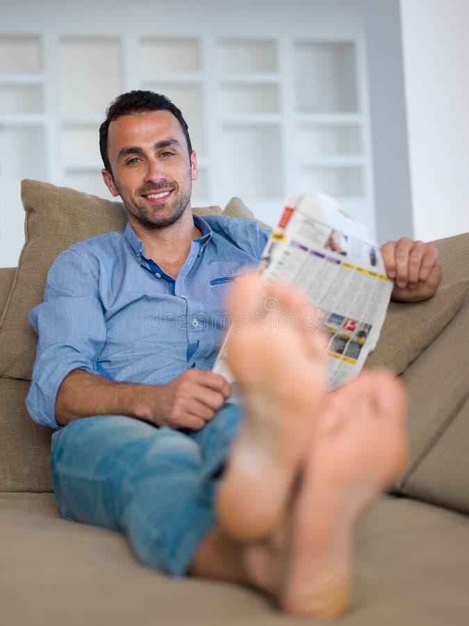 Junger Mann, der sich zu Hause auf Sofa entspannt und träumt stockfoto