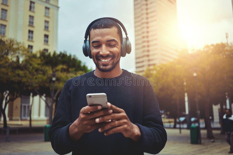 Junger Mann, der Smartphone mit Kopfhörer auf seinem Kopf betrachtet stockfotografie