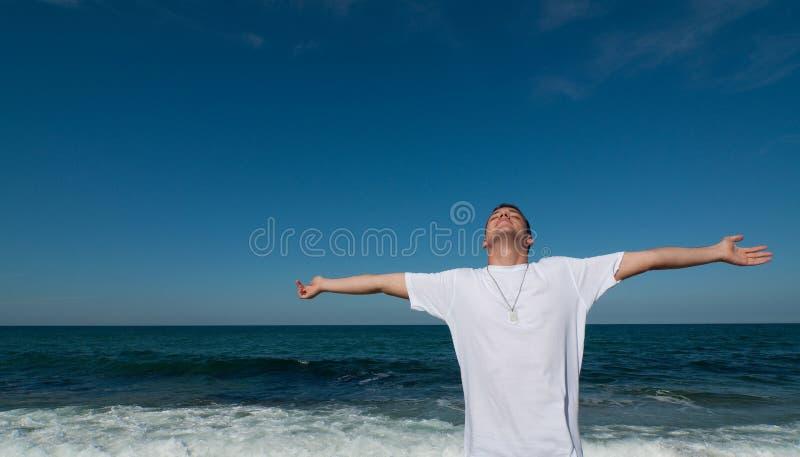 Junger Mann, der Spaß auf dem Strand hat lizenzfreies stockbild