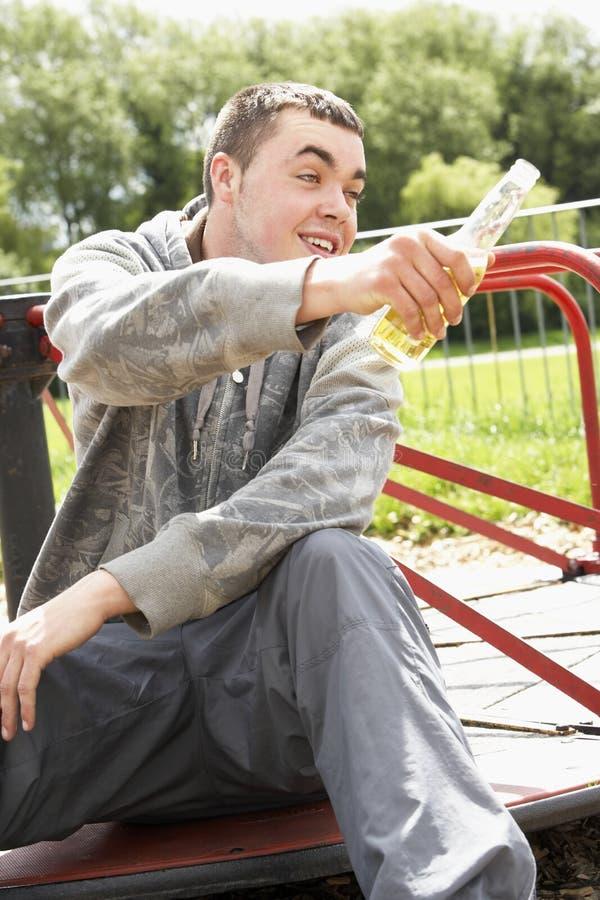 Junger Mann, der in Spielplatz-trinkendem Bier sitzt lizenzfreie stockfotografie