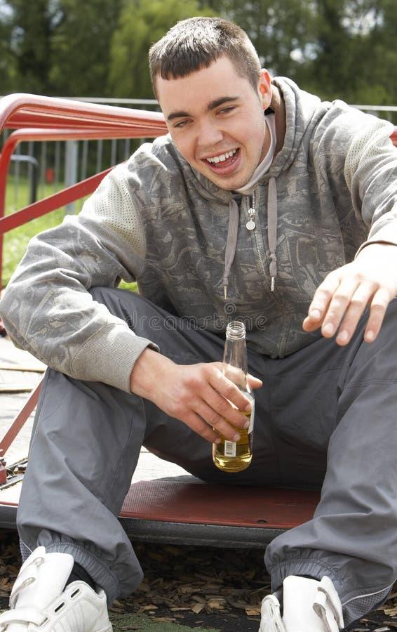 Junger Mann, der in Spielplatz-trinkendem Bier sitzt stockbilder