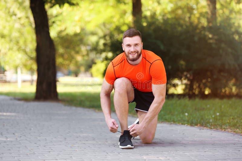 Junger Mann, der Spitzee bevor dem Laufen in Park bindet lizenzfreie stockfotos