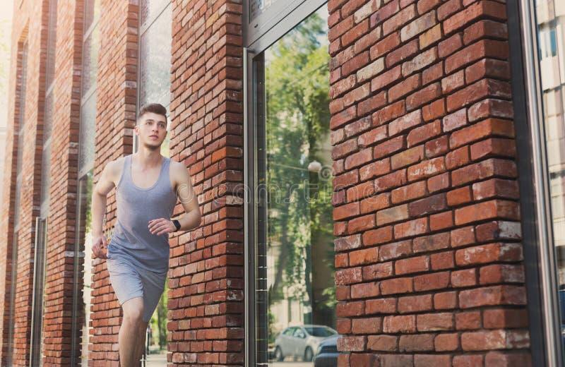 Junger Mann, der in Stadtkopienraum läuft stockfoto