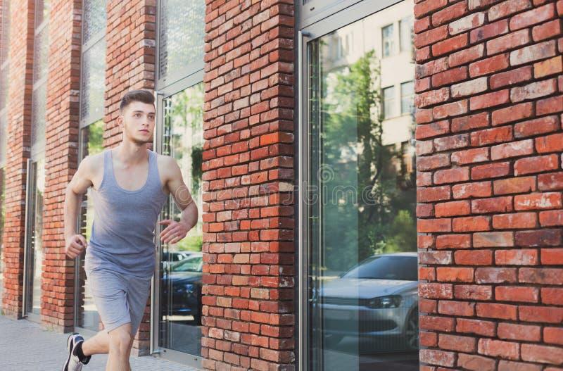 Junger Mann, der in Stadtkopienraum läuft stockfotos