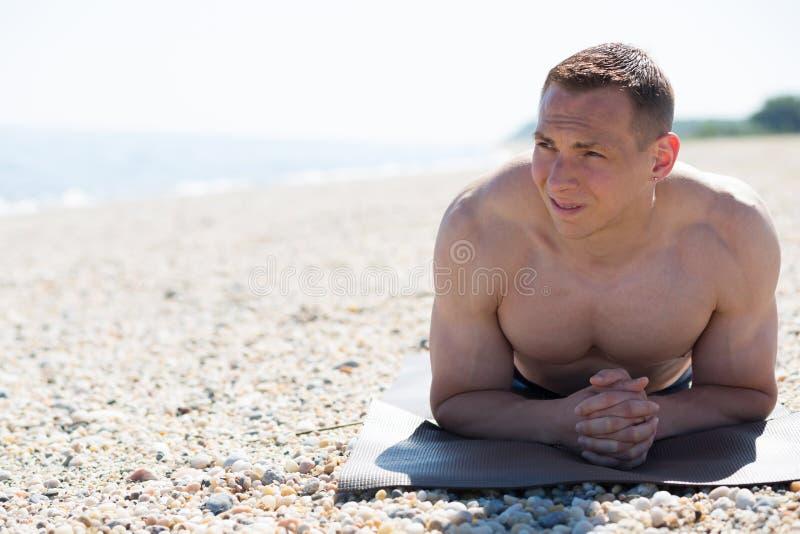 Junger Mann, der am Strand sich entspannt stockfotografie