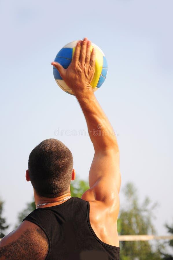 Junger Mann, der Strandvolleyball spielt stockfotos