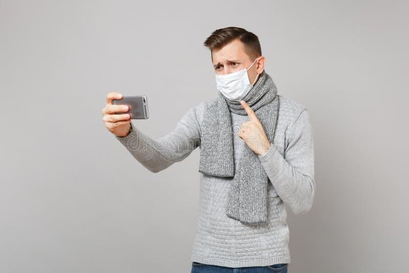 Junger Mann in der Strickjacke, sterile Gesichtsmaske des Schals, die Videoanruf mit dem Handy, Zeigefinger zeigend auf macht lizenzfreie stockfotografie