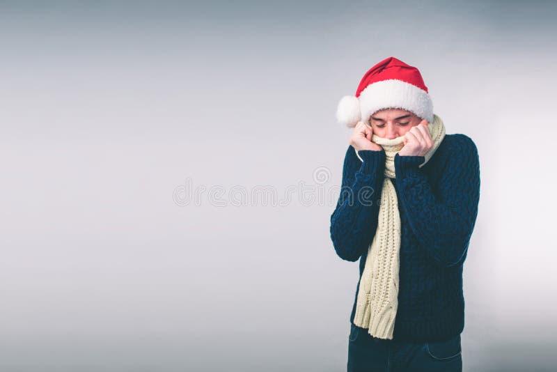 Junger Mann in der Strickjackengefühlkälte über einem weißen Hintergrund lizenzfreies stockfoto