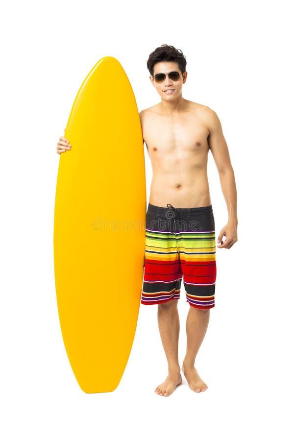 junger Mann, der Surfbrett hält stockfotos