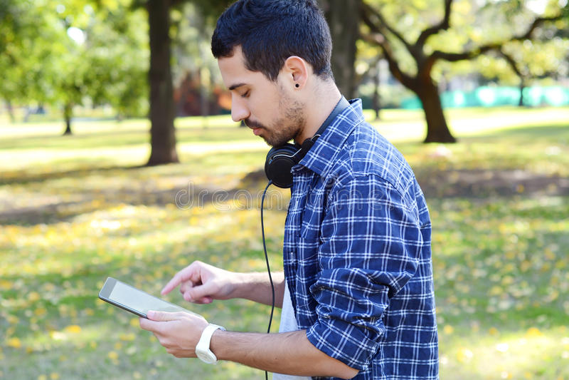 Junger Mann, der Tablette mit Kopfhörern im Park verwendet lizenzfreie stockfotografie