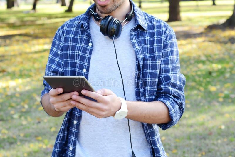 Junger Mann, der Tablette mit Kopfhörern im Park verwendet stockfotos