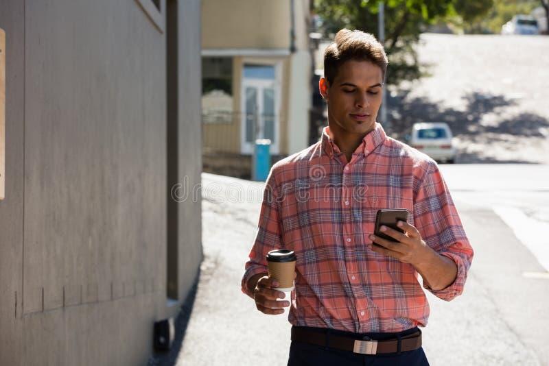 Junger Mann, der Telefon beim Gehen durch das Errichten verwendet lizenzfreies stockfoto