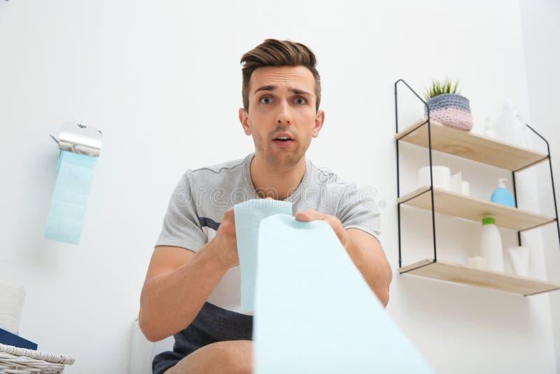 Junger Mann, der Toilettenpapier zieht lizenzfreies stockbild