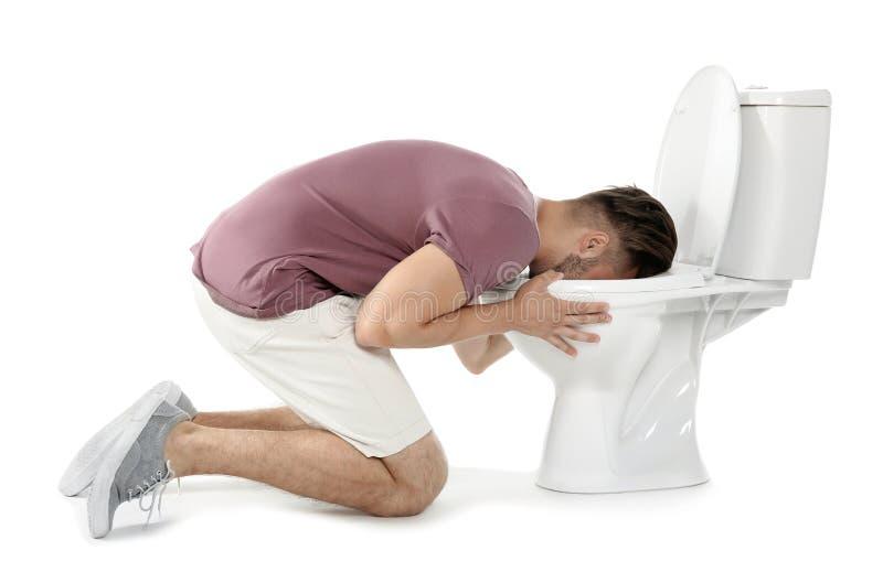 Junger Mann, der in der Toilettenschüssel sich erbricht stockbilder