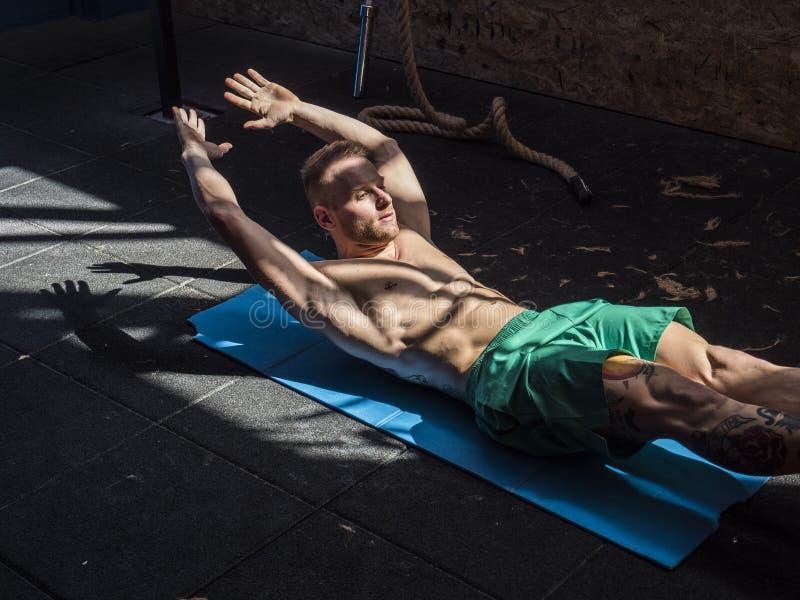 Junger Mann in der Turnhalle, die Übungen für ABS tut stockbild