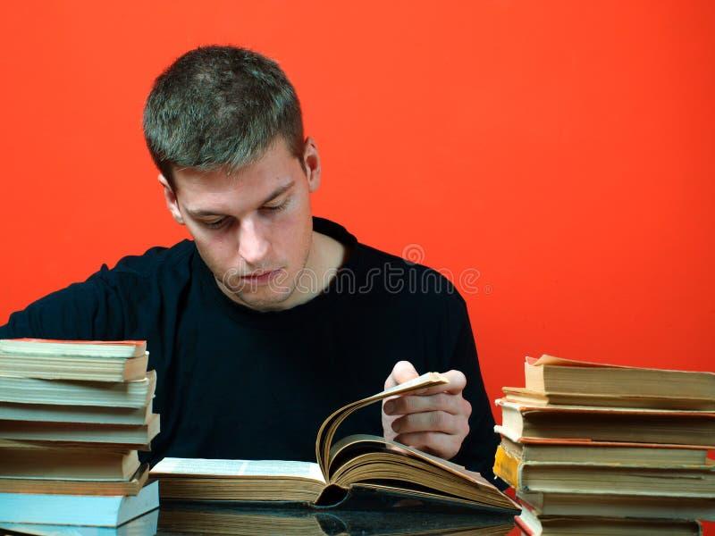 Junger Mann, der, umgeben durch Bücher studiert stockbild